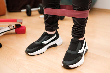 Female legs in sports leggings and sneakers doing exercises with fitness elastic bands at home during lockdown. Home workout. with resistances bands.