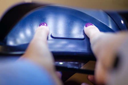 Woman drying gel polish on her nails in the LED or UV lamp. Standard-Bild