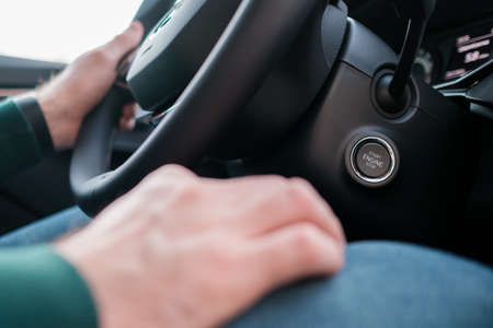 Close up mans hands on the wheel, driving a car.