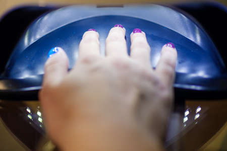 Close up of woman hand in UV or led lamp drying gel polish on her nails. Perfect manicure.