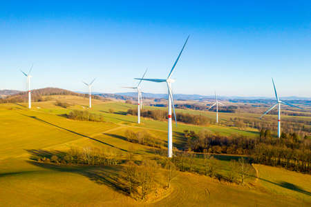 Panoramic view of wind farm or wind park, with high wind turbines for generation electricity with copy space. Green energy concept.