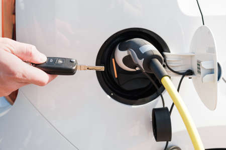 Charging an electric vehicle with a power cable supply plugged in and mans hand unblocking it with a key