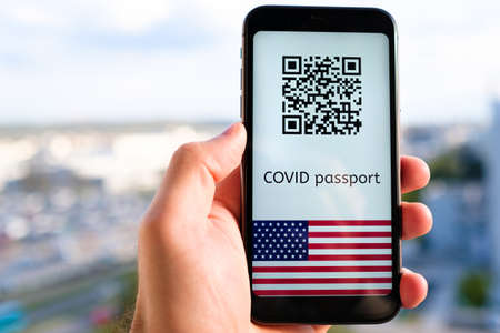 Covid passport with QR code with USA flag on the screen in smartphone in mans hand on the background of cityscape, May 2021, San Francisco, USA.