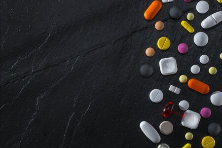 Various Tablets And Pills On A Black Stone Background