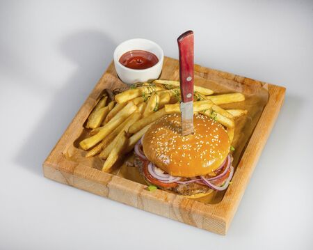 Tasty Hamburger Pierced With A Knife With French Fries And Ketchup On A Wooden Plate