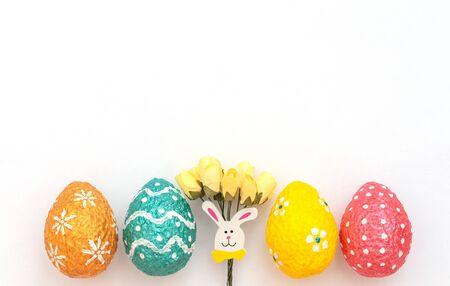 Colorful painted orange, blue, red and yellow Easter eggs with Easter rabbit and yellow spring flowers on white background. Happy Easter holiday. Flat lay style with copy space. Foto de archivo