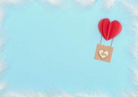 Valentine's Day blue background with red heart balloon with basket with wooden heart on it and white feathers. Valentine greeting card. Flat lay style with copy space. Love, happiness, wedding concept