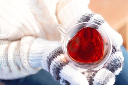 Hands in knitted mittens holding heart-shaped cup with hot drink close up. Winter and Christmas time concept. Greeting card. Happy Valentines background.