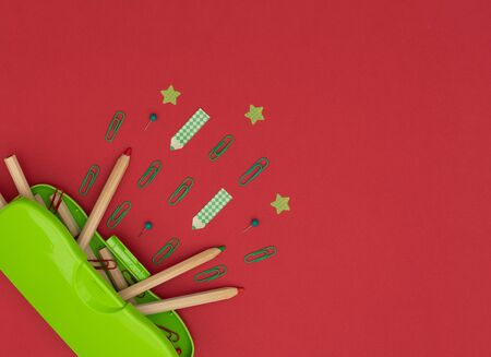 Green pencil case, wooden pencils, red and green clips and pins, pencil and star shaped paper stickers on red background. School and office supplies, stationary. Back to school concept. Flat lay style