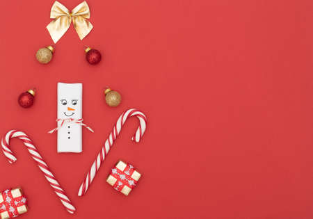 Christmas red background with snowman, candy canes, gift boxes with red ribbon, red and gold balls and gold bow. New Year greeting card. Christmas, New Year concept. Flat lay style with copy space. Zdjęcie Seryjne