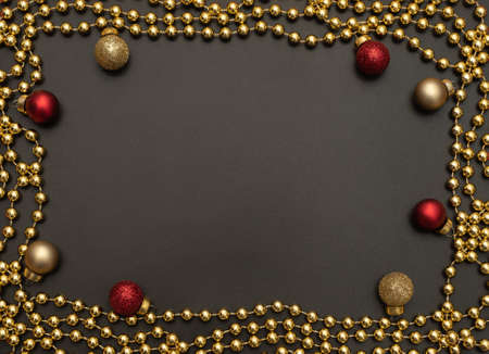 Christmas black background with golden beads and red and golden Xmas decorations. Flat lay style. New Year greeting card.
