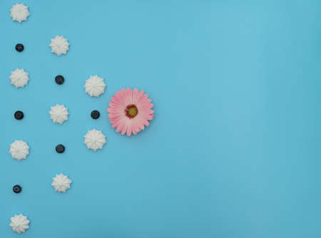 Delicious white merengues, fresh blueberries and a flower on blue background. Happy day, breakfast, good morning concepts. Time for tea. Greeting or invitation card. Flat lay style with copy space.