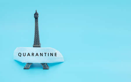 """Medical face mask with text """"Quarantine"""" covers travel attraction on blue background. Biohazard, 2019-nCoV, COVID-19. The concept of isolation, quarantine and closed world in pandemic. Flat lay style"""