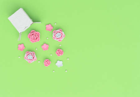White box with explosion of beads and flowers made of foamiran on green background. Mother day, Valentine day, Wedding, Birthday party concept. Greeting or invitation card. Flat lay with copy space.
