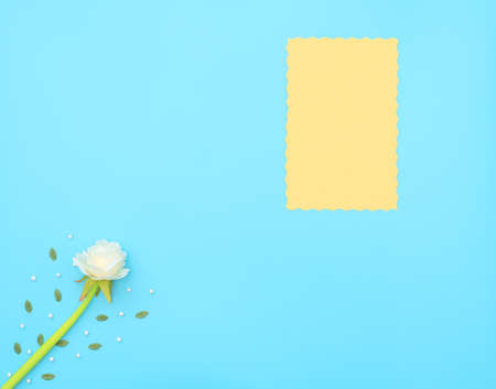 Yellow paper sheet and white flower with green leaves and white beads on blue background. Mother day, Valentine day, Wedding, Birthday concept. Greeting or invitation card. Flat lay with copy space. Banque d'images