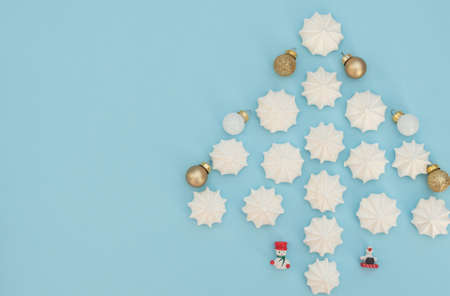 Christmas tree made with white meringues with golden and white Christmas balls and wooden Xmas decorations on light blue background. Flat lay style with copy space. New Year greeting card.
