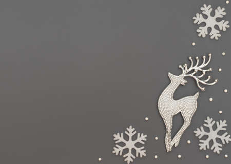 Christmas or winter gray background with one deer and white snowflakes and beads. New Year greeting card. Christmas, New Year or winter concept. Flat lay style with copy space.