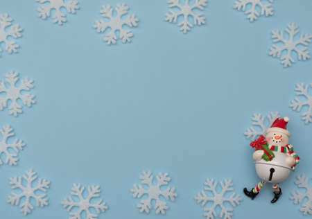 Christmas blue background with Christmas decorations and white snowflakes. New Year greeting card. Flat lay style.