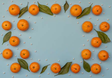 Blue background with orange tangerines with green leaves and white beads like snow. Christmas greeting card. Flat lay style.