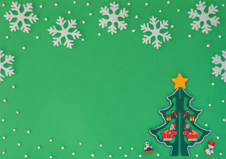 Christmas green background with wooden Christmas tree and white snowflakes. New Year greeting card. Flat lay style.