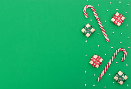 Christmas green background with two candy canes, gift boxes with red and green ribbon and white beads. New Year greeting card. Christmas, New Year concept. Flat lay style with copy space. Banque d'images