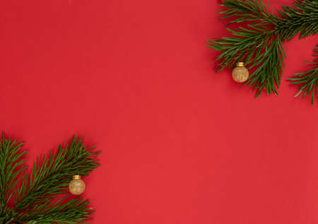 Christmas, New Year or winter red background with fir tree branches and gold balls. Xmas and Happy New Year holiday concept. Greeting or invitation card. Flat lay, top view style with copy space. Banque d'images