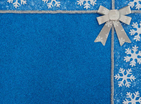 Christmas or winter blue background with white snowflakes, silver tinsel, bow and snow. New Year greeting card. Xmas, New Year or winter concept. Flat lay style with copy space. Banque d'images