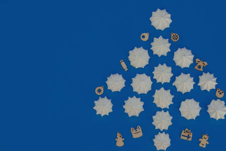 Christmas tree made with white meringues with wooden Xmas decorations on blue background. Flat lay style with copy space. New Year greeting card.