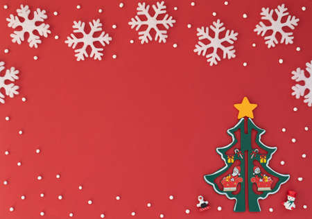 Christmas red background with wooden Christmas tree and white snowflakes. New Year greeting card. Flat lay style.