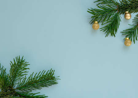 Christmas, New Year or winter blue background with fir tree branches and small gold balls. Xmas and Happy New Year holiday concept. New Year greeting card. Flat lay, top view style with copy space. Banque d'images