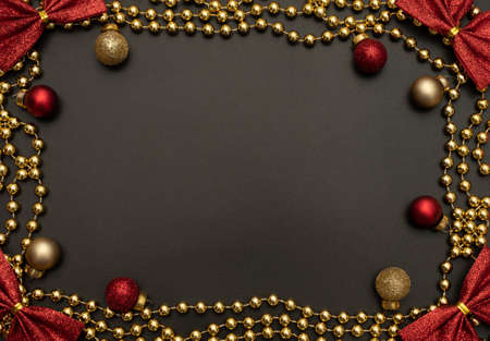 Christmas black background with golden beads, red and golden Christmas decorations and red bows. Flat lay style. New Year greeting card.