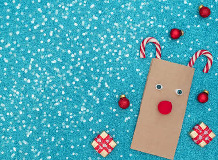 Christmas deer made of craft bag and two Xmas canes with two gift boxes, red balls on blue background with white snow. New Year greeting card. Xmas and New Year concept. Flat lay style with copy space