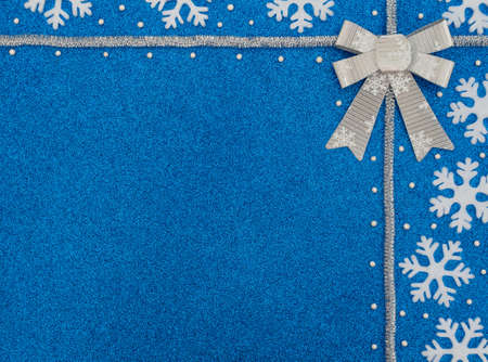 Christmas or winter blue background with white snowflakes, beads, silver tinsel and bow with snowflakes. New Year greeting card. Xmas, New Year or winter concept. Flat lay style with copy space.