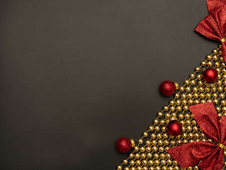 Christmas black background with golden beads, red Xmas decorations and red bows. Flat lay style. New Year greeting card.
