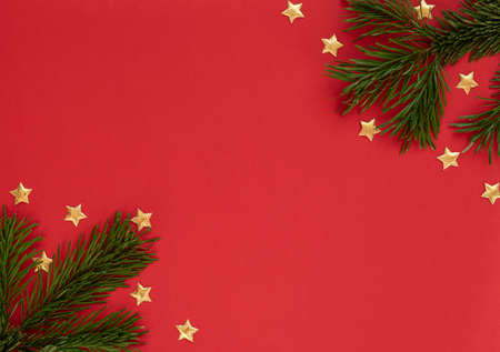 Christmas, New Year or winter red background with fir tree branches and small gold stars. Xmas and New Year holiday concept. Greeting or invitation card. Flat lay, top view style with copy space. Banque d'images