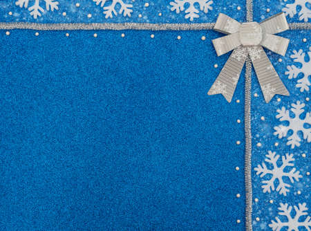Christmas or winter blue background with white snowflakes, beads, silver tinsel, bow and snow. New Year greeting card. Xmas, New Year or winter concept. Flat lay style with copy space.