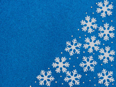 Christmas or winter blue background with white snowflakes and beads. New Year greeting card. Christmas, New Year or winter concept. Flat lay style with copy space.