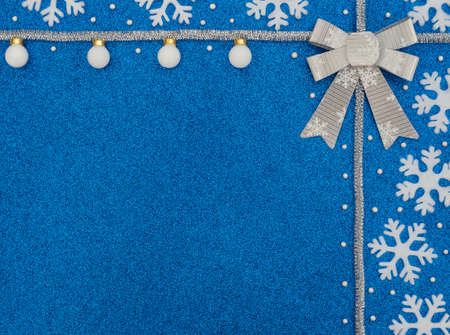 Christmas or winter blue background with white snowflakes, balls, beads, silver tinsel and bow. New Year greeting card. Xmas, New Year or winter concept. Flat lay style with copy space.