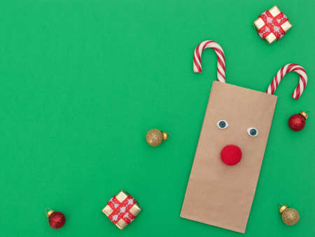 Christmas deer made of craft shopping bag and two Xmas canes with gift boxes and Xmas balls on green background. New Year greeting card. Christmas and New Year concept. Flat lay style with copy space. Banque d'images