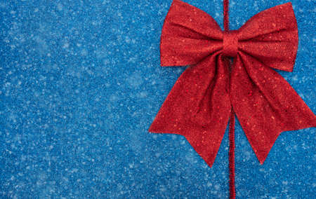 Christmas or winter blue background with red tinsel, bow and snow. New Year greeting card. Xmas, New Year or winter concept. Flat lay style with copy space. Banque d'images