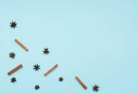 Cinnamon sticks and anise stars on blue background. Cooking concept. Winter and holiday spices. Flat lay, top view with copy space for your text. Banque d'images