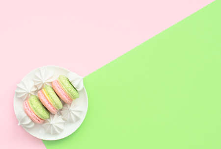 Delicious macarons with white merengues on white plate on double green and pink background. Happy day, breakfast, good morning concepts. Greeting or invitation card. Flat lay style with copy space.