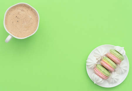 The cup of cappuccino and delicious macarons with white merengues on white plate on green background. Happy day, breakfast, good morning concepts. Greeting card. Flat lay style with copy space.