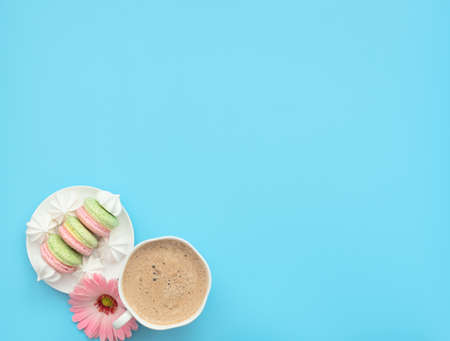 The cup of cappuccino and delicious macarons with white merengues on white plate on blue background with pink flower. Happy day, breakfast concepts. Greeting card. Flat lay style with copy space. Banque d'images