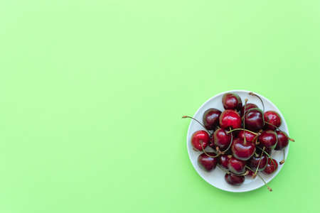 Fresh sweet cherries on white plate on green background. Healthy eating, minimalism concepts. Flat lay style with copy space for your text. Banque d'images