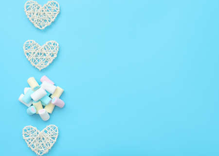 A lot of delicious white, yellow, blue and pink marshmallows with white rattan hearts on blue background. Happy day, breakfast, love, good morning concepts. Valentine greeting card. Flat lay style.