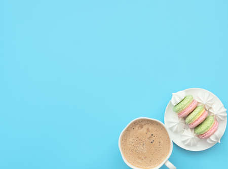 The cup of cappuccino and delicious macarons with white merengues on white plate on blue background. Happy day, breakfast concepts. Greeting card. Flat lay style with copy space. Banque d'images