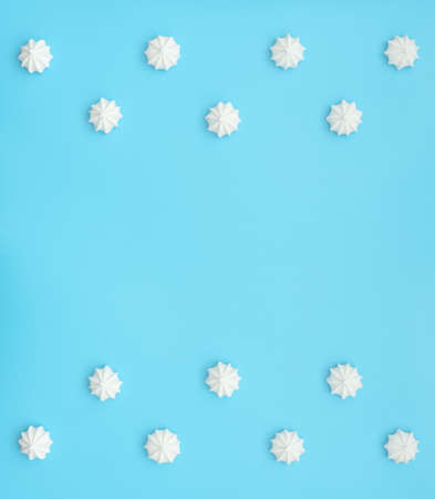 Delicious white merengues on blue background. Happy day, breakfast, good morning concepts. Time for tea or coffee. Greeting or invitation card. Flat lay style with copy space.