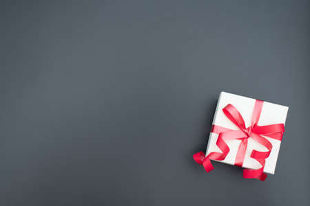 White giftbox with red ribbon on black background. Father day, Valentine day, Wedding, Birthday, Christmas concept. Male holiday concept. Greeting or invitation card. Flat lay style with copy space.