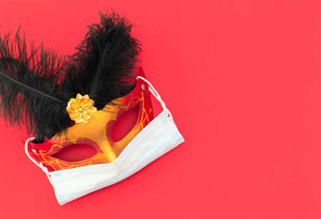 Masquerade mask with medical protective face mask on red background. Xmas holiday during COVID-19 pandemic in the world. Winter, New Year greeting card. Flat lay style with copy space for your text.